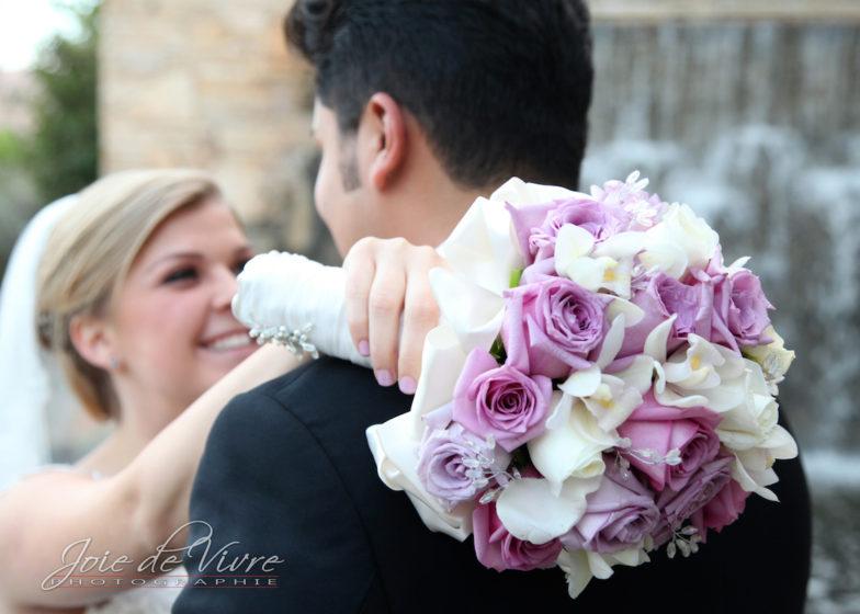 Happy bride, groom and bride hugging, photographer